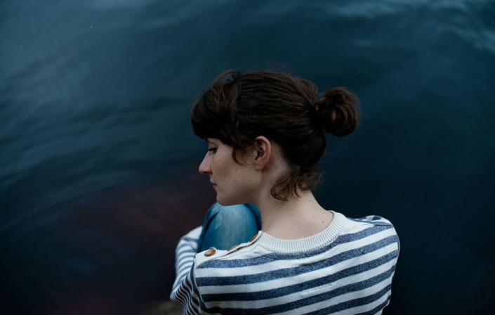 photography of a woman sitting by the water